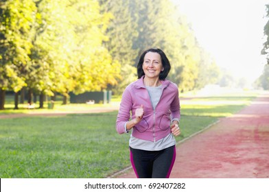 Portrait of elderly woman running in the park in early morning. Attractive looking mature woman keeping fit and healthy.