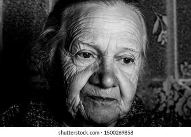 Portrait of elderly woman in rustic interior. Toned.