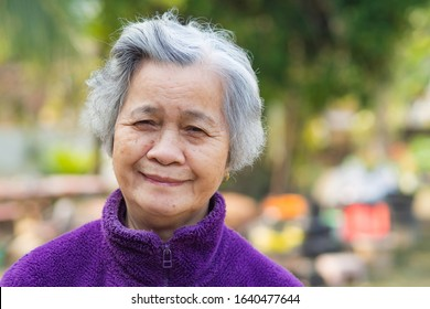Portrait of elderly woman with short white hair and standing smile in garden. Asian senior woman healthy and have positive thoughts on life make her happy every day. Health care concept