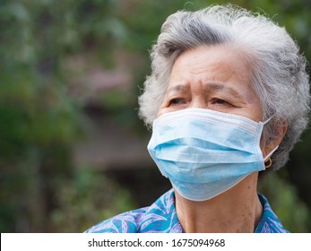 Portrait of elderly woman with short white hair, wearing face mask for health because have air pollution PM 2.5. Mask for protect virus, bacteria, pollen grains. Health care concept