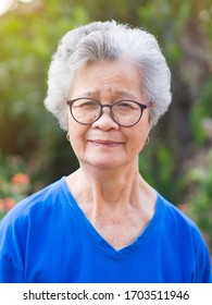 Portrait of elderly woman with short white hair standing smile and looking at the camera in garden. Asian old woman healthy and have positive thoughts on life make her happy every day. Health concept