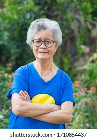 A portrait of an elderly woman short white hair wearing glasses smiling with arms crossed and looking at the camera while standing in a garden. Concept of old people and health care