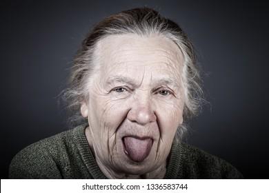 Portrait of elderly woman. Shows tongue. Toned.