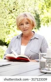 Portrait of elderly woman sitting at home in the garden and reading book.