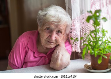 Portrait of elderly woman sitting at the table in the house.