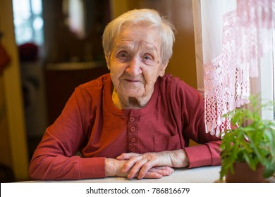Portrait of an elderly woman sitting at table in the house.