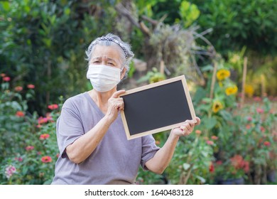 Portrait of elderly woman standing holding a blackboard and wearing face mask for healthy because have air pollution PM 2.5. Mask for protect Virus, Bacteria, Pollen Grains. Healthcare concept