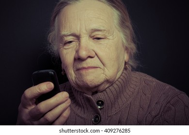 Portrait of elderly woman with telephone on dark background. Toned.