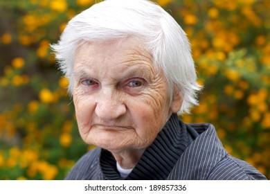 Portrait of an elderly woman walking in the garden
