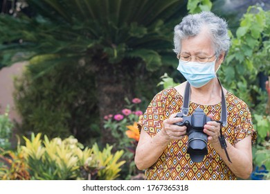 A portrait of an elderly woman wearing a face mask and holding digital camera while standing in a garden. New normal. Concept of old people, healthcare and photography