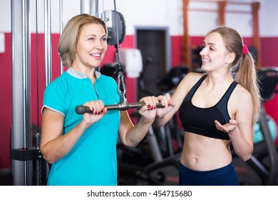 Portrait of elderly and young women doing powerlifting on machines in jym