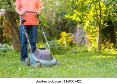 portrait of eldery senior man working in the summer garden walking on grass field