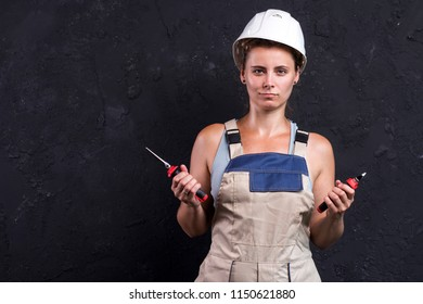 Portrait of electrician woman in uniform and white helmet holds in hand wire-cutters and nippers. Female worker in workwear with electric tools in her hands.