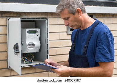 Portrait Of Electrician Worker Inspecting Electric Meter