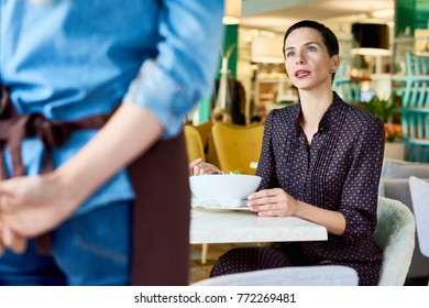 Portrait of elegant adult woman complaining about food quality and taste to young waitress in cafe, copy space