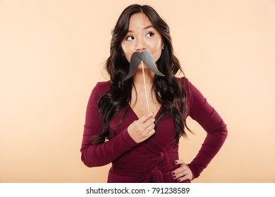 Portrait of elegant asian female in pretty maroon dress having fun on peach background, putting artificial mustaches over mouth