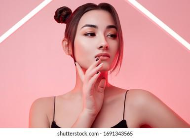 Portrait of elegant beautiful Asian woman in a fashionable raincoat around colourful bright neon uv lights posing in studio