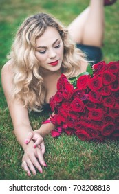 Portrait of elegant beautiful blonde woman is wearing black fashion dress lying on green lawn holding with big bouquet of 101 red roses