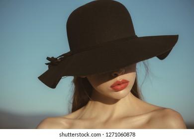 Portrait of elegant beautiful woman in a black wide hat on blue sky background.