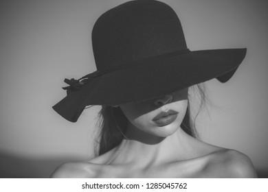 Portrait of elegant beautiful woman in a black wide hat on blue sky background