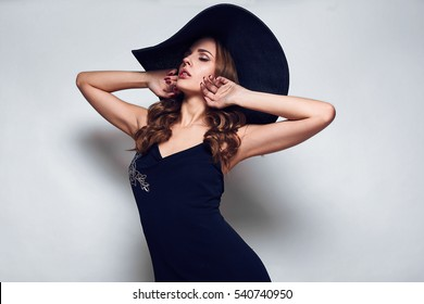 Portrait of elegant beautiful woman in a black dress and wide hat isolated on white background in studio