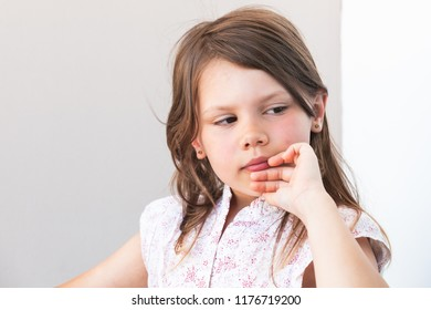 Portrait of elegant blond little girl, close-up photo over white wall background