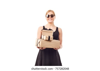 Portrait of elegant blonde woman in black dress and sunglasses holding gift boxes