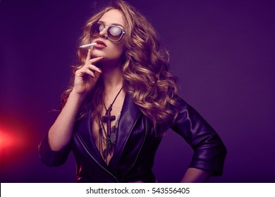 Portrait of elegant blonde woman in glasses smoking a cigarette on colorful background in studio