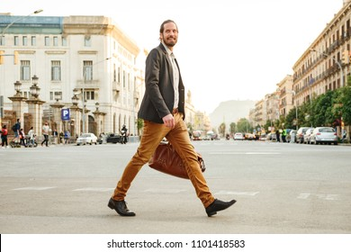 Portrait of elegant businessman in jacket laughing while crossing road in megapolis with leather male bag in hand
