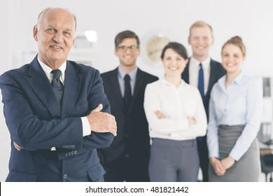 Portrait of an elegant elder businessman with his young employees in the blurred background