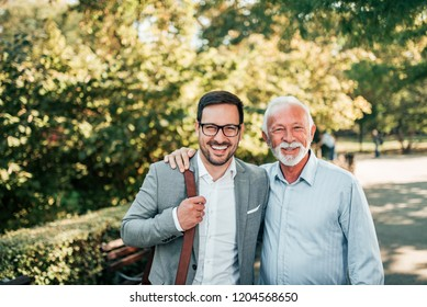 Portrait of elegant father and son outdoors.