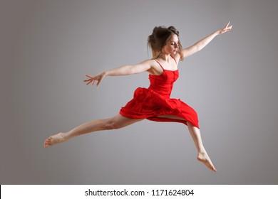 Portrait of elegant female dancer in red dress jumping against gray background