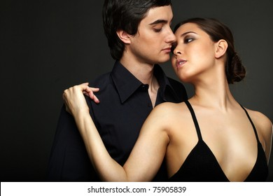 Portrait of elegant girl with handsome man near by on black background