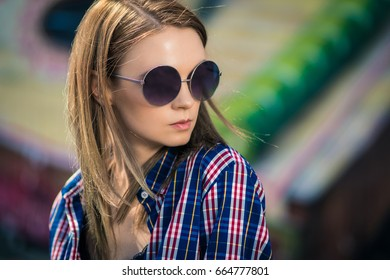 Portrait of elegant girl with long hair in sunglasses smiling in city park