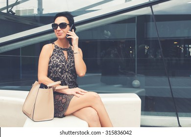 Portrait of elegant lady talk on mobile phone while relaxing after walking on the street in summer day, confidence female business woman calling with smart phone while sitting outdoors in summer day