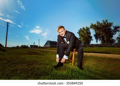 Portrait of elegant man in black suit putting on shoe at green summer grass lawn background.