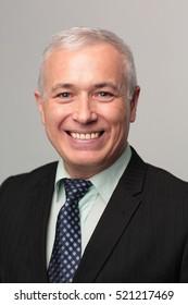 Portrait of an elegant  mature business man on grey background