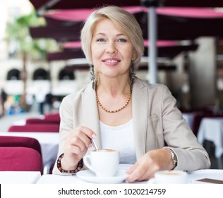 Portrait of elegant mature female who is enjoying of lunch with coffee in cafe.
