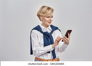 Portrait of elegant middle aged caucasian woman wearing business attire and earphones holding, using smartphone while standing isolated over grey background. Horizontal shot