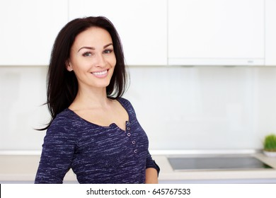 Portrait of elegant middle aged woman standing in kitchen at home