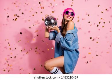 Portrait of elegant party youth holding mirror ball wearing denim jeans jacket eyewear eyeglasses isolated over pink background