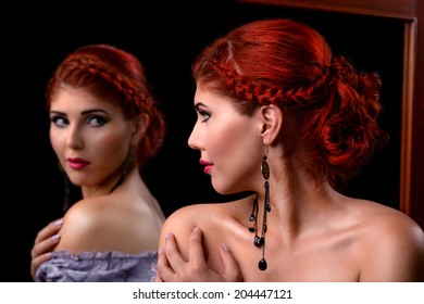 Portrait of an elegant redhead woman looking in the mirror