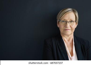 Portrait of elegant senior woman standing against dark wall