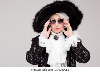 Portrait of elegant, senior woman from upper class wearing sunglasses and expensive hat of noblesse isolated in studio.