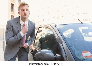 Portrait of elegant suited business man grooming using a car mirror doing up his tie, getting ready for interview meeting, sunny city outdoors. Fashion accessories for professional people, image care.