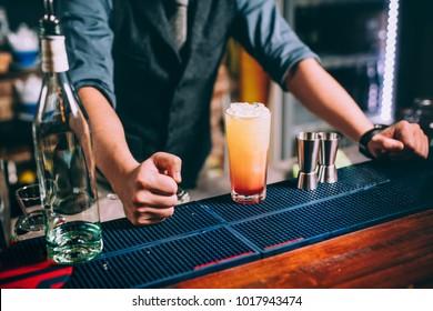 Portrait of elegant and vintage bartender, barman preparing orange based vodka and tequila cocktails