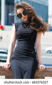 portrait of elegant woman in black dress walking in city