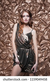 Portrait of elegant woman wearing glossy dress posing in the studio