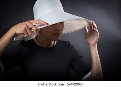 Portrait of elegant woman with white hat over black background