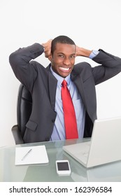 Portrait of an elegant young Afro businessman with laptop at desk against white background